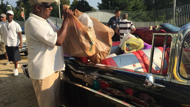 Soul Riders Auto Club member James Knott of Newport hefts bags of goodies from his '57 Chevy – named Pop Pop's Toy – Sunday at Nemours/Alfred I. duPont Hospital for Children in Rockland.
