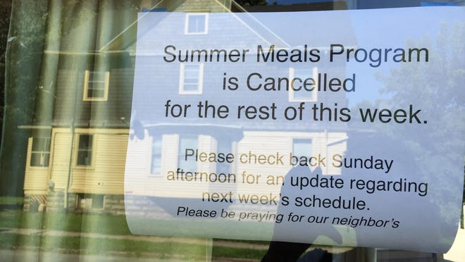 A sign announces the cancellation of the summer meals program for the week after a volunteer was shot outside the 441 Ministries building.