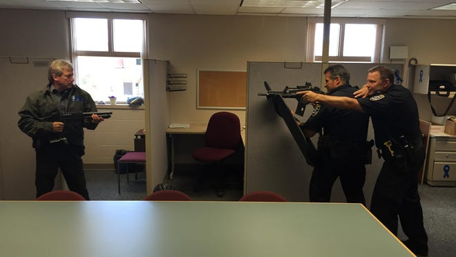 From left, Community Service Worker Danny Harms, Capt. Larry Zimney and Officer Rob Weyer simulate a situation in which the officers encounter a gunman during the Manitowoc Police Department's training for active killer scenarios.