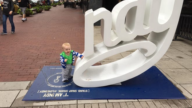 """Beckett Triest, 2, poses as a lowercase """"I"""" with one of three #LoveIndy sculptures around Downtown Indianpolis."""