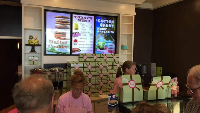 Patrons step up to the counter at Gigi's Cupcakes during a soft opening Sunday.