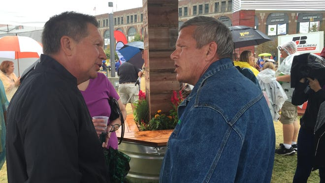 Ohio Gov. John Kasich, left, visits with Iowa Agriculture Secretary Bill Northey Tuesday at the Iowa Farm Bureau booth at the Iowa State Fair.