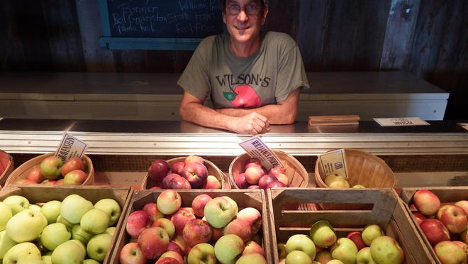 Paul Rasch, the owner of Wilson's Orchard in Iowa City, poses with bushels of his own orchard's apples on Aug. 14.