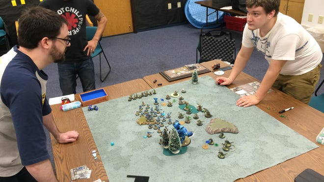 As Jason Capek (center) watches, Matt Schmidkamp, left, and Chris Smith, Rudolph, contemplate moves during a game of Warmachine at the Charles and JoAnn Lester Library in Nekoosa.