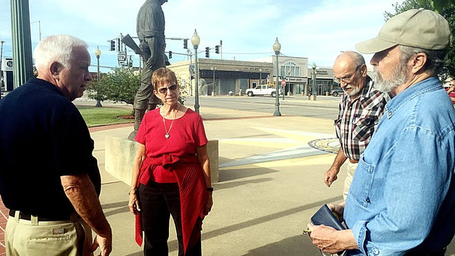 Mayor Joe Dillard, at left, council members Jennifer Baker and Carl Graves, and sculptor Ron Moore look over a possible site for a bust on the Mountain Home Plaza.