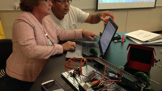 Collier County teachers Katie Sullivan and Olivio Pozo concentrate on programming their robot Wednesday at FGCU during Project Lead the Way training workshop.