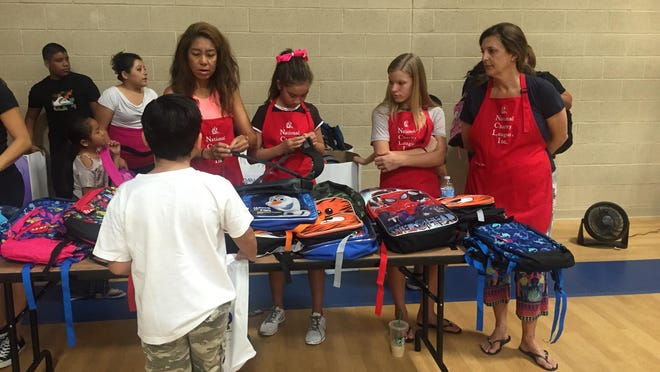 Volunteers show a boy how to adjust the straps of the backpack he received Saturday during the 12th annual backpack bonanza at the Coachella Valley Rescue Mission in Indio Saturday, August 22, 2015.