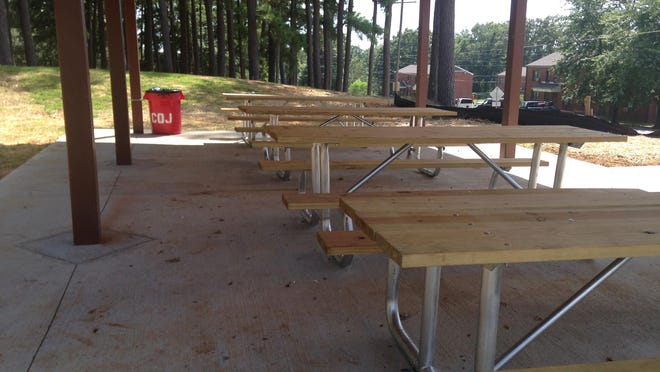The city placed picnic tables at Forest Hill Park, which remains closed more than a year after its set date of completion.