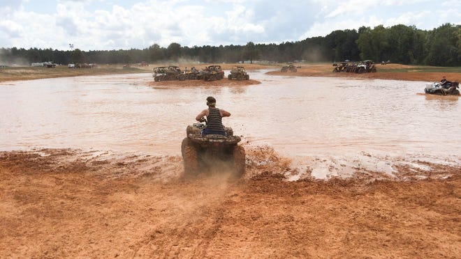 ATV riders tackle a large mud pit at Muddy Bottoms over Labor Day weekend. Two people were killed at the park the same weekend.