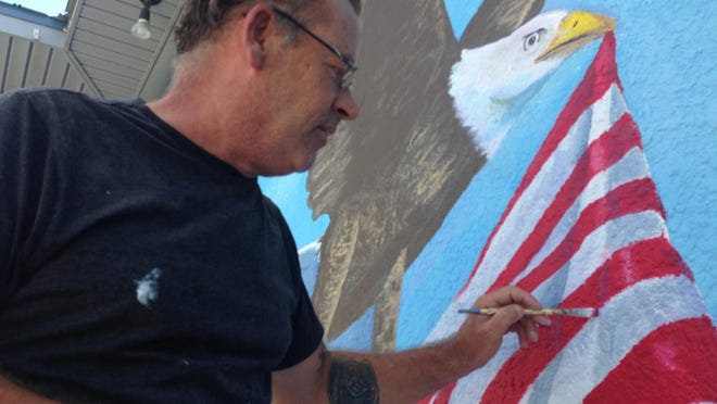 Erik Schlake, a Cape Coral muralist, is painting a new mural to replace an older painting on the clubhouse wall at Tamiami Village in North Fort Myers.