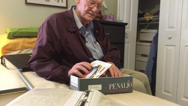 Wendell Meggs looks through pictures and memorabilia, some of it from his service during World War II, in his room at Morningside.