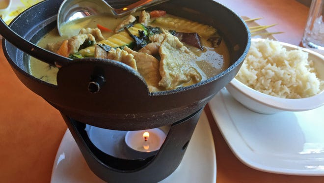 Thai green curry with pork and steamed rice served in an iron pot with a tea candle