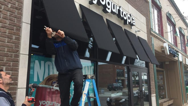 Chadi Elassad, standing on ladder, and Zein Boussi are helping get Yogurtopia ready for its April 14 grand opening.