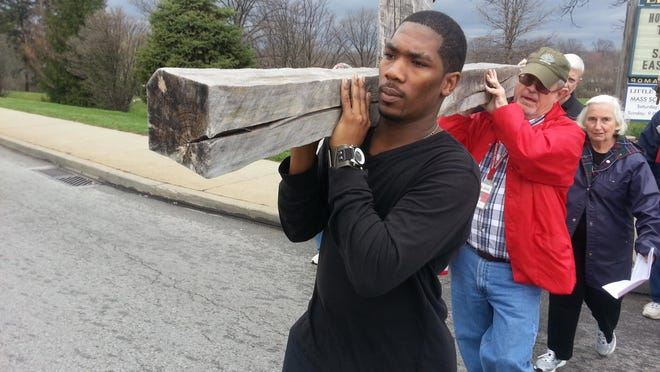 Participants carry a heavy, wooden cross through Mount Airy as part of an annual Good Friday Way of the Cross program.