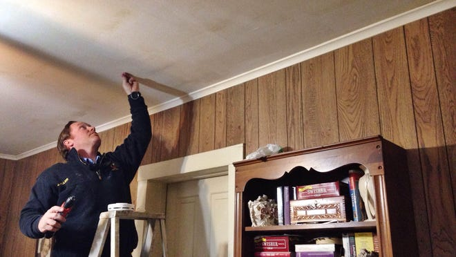 Firefighter Jeff Miller installs a free smoke detector in a Bemis home Saturday for 'Get Alarmed, Tennessee!'