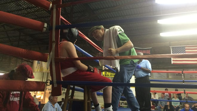 A manager from Augusta, Ark., talks with his fighter, Landon Headley, between rounds during Headley's loss to Ladarious Taylor during the Golden Gloves boxing tournament at Jackson Boxing Club on Friday.