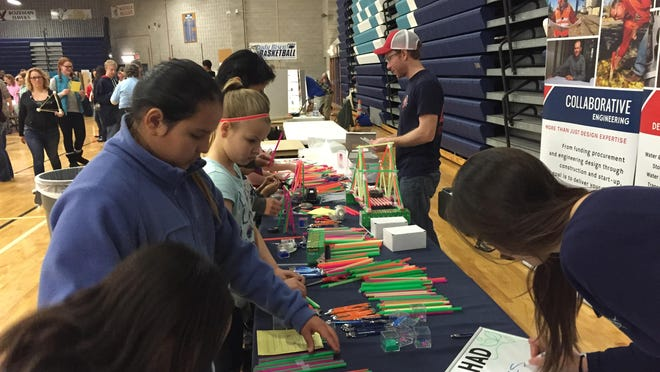 Kids build bridges out of straws with the help of a structural engineer from TD&H at the Great Falls Public Schools' STEAM Expo on April 2, 2016.