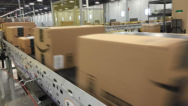 Packages zip down an Amazon conveyor belt in Tracy, Calif.