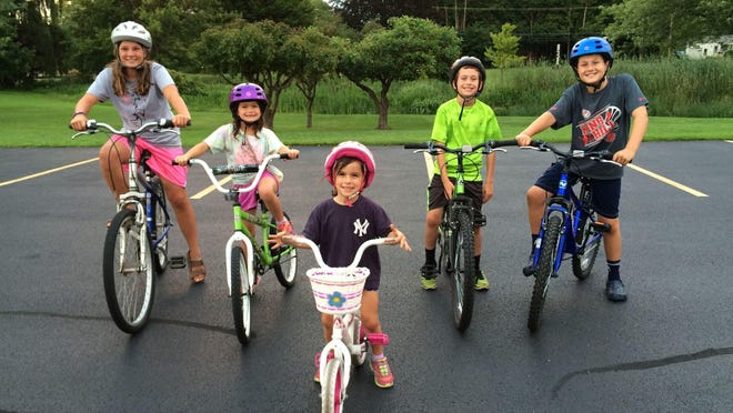 Lucy Buss, center, learns to ride a bicycle without training wheels last summer with a little help from her siblings and neighbors. Pictured with her are: Grace Burns, left, Ella Buss, Tyler Buss and Jack Burns.