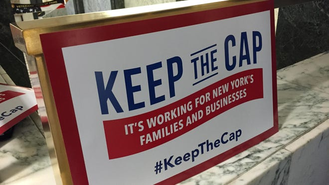 Business groups at the state Capitol in 2015 held these posters to push the state Legislature to keep the property-tax cap, which lawmakers ultimately extended for four years.