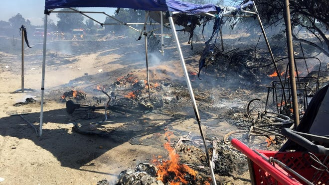 Flames still burned Saturday afternoon in campsite for homeless people on the north bank of the St. Johns River, just north of Visalia, after a fire burned through part of the campsite.