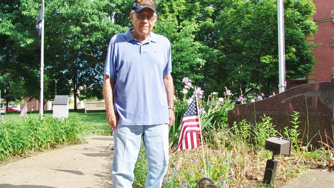 George Leach stands by a World War II marker on the court square during the Memorial Day service.