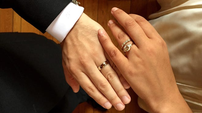 Amber Marlow shows the ringed hands of Marlow and her husband, Marley Jay, after their wedding, in Stone Ridge, N.Y.