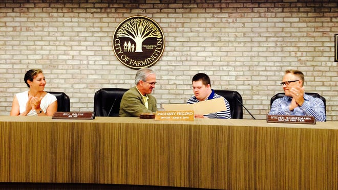 Mayor Bill Galvin hands Zachary Feczko a proclamation while city council members applaud.