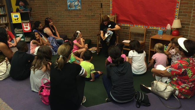 Kids, along with their moms and caregivers, gather around librarian Laurie Scott for story time.