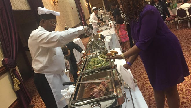 Urban League of Rochester President William G. Clark serves up some sides during the 26th annual Distinguished Male Cooks Event