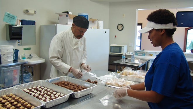 George Jones Sr. and his daughter, Martha Young, package brownie bites in a July 2016 Tribune file photo at Grandmom Minnie's Munchies at 1146 Walnut St. The storefront has since closed. Martha and her brother, Joshua Jones, were killed in a double homicide Monday in Canal Lewisville.