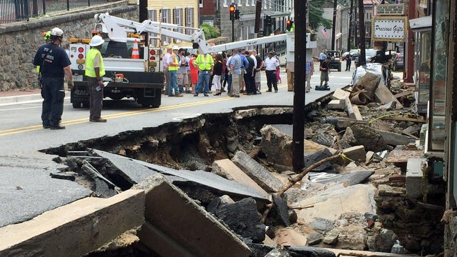 Workers gather by street damage after Saturday night's flooding in Ellicott City, Md., Sunday, July 31, 2016. Historic, low-lying Ellicott City, Maryland, was ravaged by floodwaters Saturday night, killing a few people and causing devastating damage to homes and businesses, officials said. Kevin Rector/The Baltimore Sun via AP