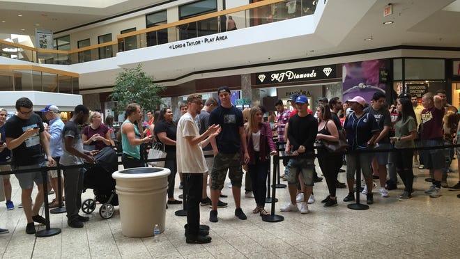 Fans of Kanye West wait in line inside Lakeside Mall Thursday to visit the musician's new pop-up store.