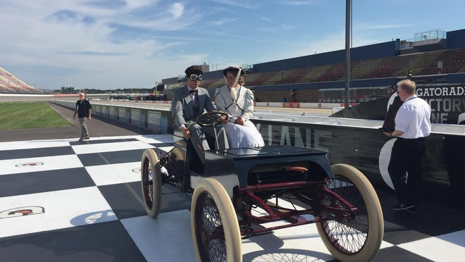 """Brad Keselowski and Kelli Stavast take a replica of Henry Ford's """"Sweepstakes"""" for a spin around MIS."""