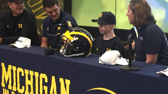 From left, U-M coach Jim Harbaugh, quarterback John O'Korn, Larry Prout Jr., and his mother Kathryn, sit at a table in the lobby of Schembechler Hall for Larry's commitment announcement.