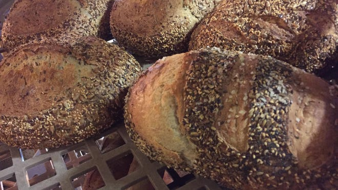 "Loaves of Blue Oven Bakery ""Bad Boy"" sourdough bread at right are on display at the Fort Thomas Farmers Market inside Fort Thomas Antiques and Design Center. The ""Bad Boy"" is rolled in fennel, and seeds, flax seed, poppy seed, sesame seeds and topped with sea salt."
