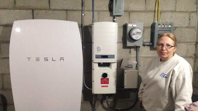 """Rhonda """"Honey"""" Phillips poses next to a Tesla Powerwall battery and inverter connected to a solar panel array in her yard in Middletown Springs. Phillips is one of the growing number of Green Mountain Power customers using the Tesla battery to store solar energy when her panels aren't collecting it. GMP has been working to link solar energy with battery storage on both a large and small scale."""