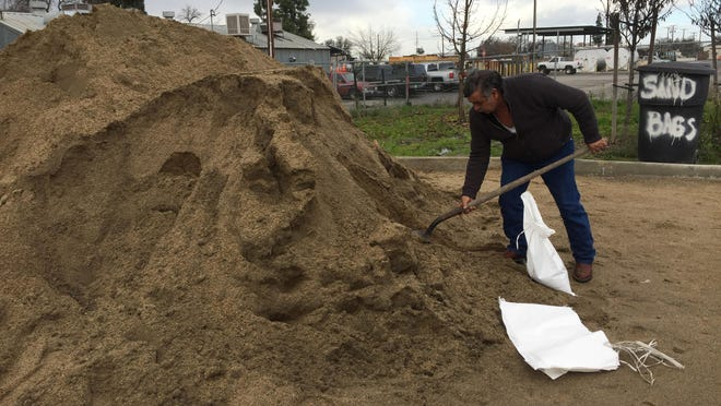 Jose Sanchez fills a sand bag in his car's trunk Thursday morning. Visalia is hosting a free, self-service sand bag station ahead of the storm systems expected to move through the area.