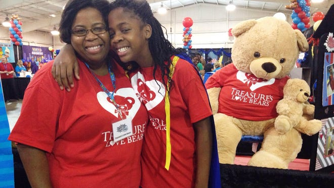 Tierra and Treasure Thaxton distribute teddy bears at the 2015 BabyFest and Kids Expo.