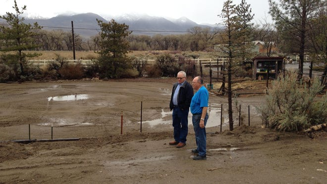 Bill Kennedy and his neighbor, John Gavin, look at the Kennedys' now-barren yard. Gavin's flooded alfalfa field is in the background.