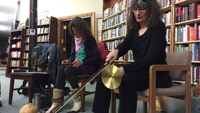 Julia Becker, left, picks out some notes as Janet Henderson plays a hand cymbal with a violin bow.