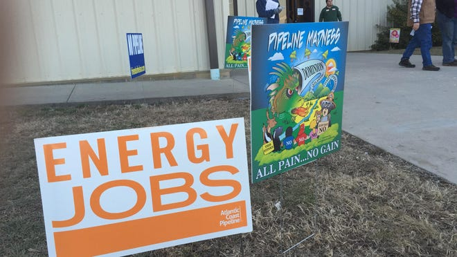 Signs for and against the proposed Atlantic Coast Pipeline welcome visitors at Augusta County Expo where members of the community met Dominion representatives on Jan. 20, 2015.