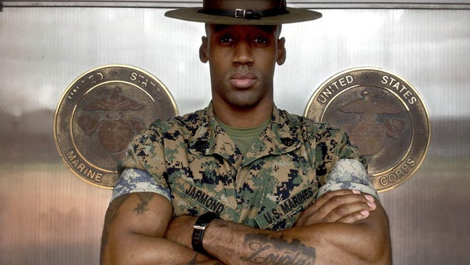 """Staff Sgt. Jason Jarmond stands near the famous """"Silver Hatches"""" at Marine Corps Recruit Depot Parris Island, S.C. Jarmond, a senior drill instructor at the depot, has a tattoo and wears a bracelet in memory of friend and fellow Marine, """"Bull."""""""