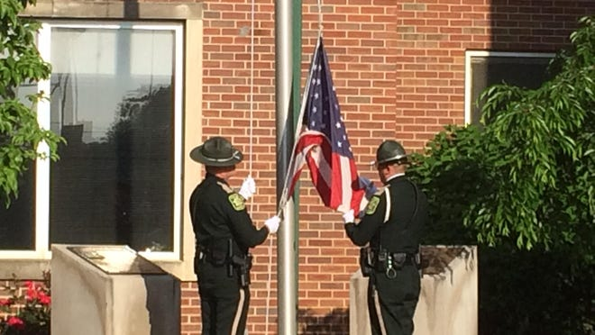 Officers raise the flag as part of a flag detail during the ceremony on Monday, May 14, 2018.
