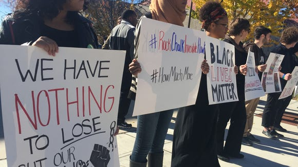 """Rock Chalk Invisible Hawk student activists hold signs with sayings like """"Black Lives Matter"""" on Wescoe Beach at the University of Kansas campus Thursday afternoon. (Emily Donovan / USA TODAY College)"""