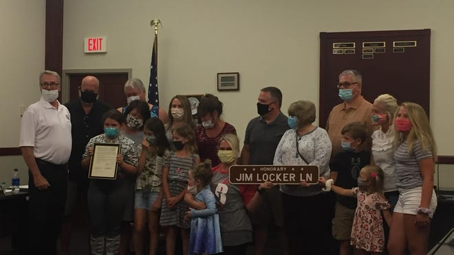 """The family of the late Jim Locker attended Monday's New Philadelphia City Council meeting when Locker was honored for his years of service to the community. Council President Don Kemp (left) presented them with a framed copy of an ordinance designating a portion of Bank Lane SE as """"Honorary Jim Locker Lane."""""""