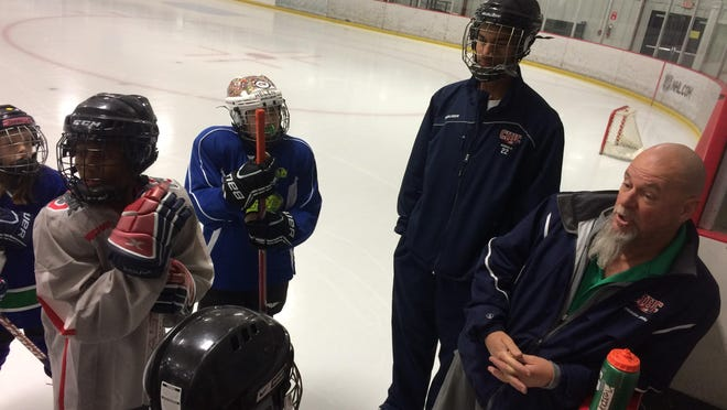 John Haferman, right, talks to players during a practice Columbus Ice Hockey Club. Next to Haferman is Akeem Adesiji, a former player who in 2016 won a Thurgood Marshall scholarship, given to top youth hockey players. He now coaches in the program.