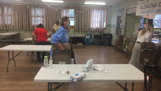 Volunteers work Friday to get the Warren Township Community Center in New Cumberland ready for its reopening on Monday.