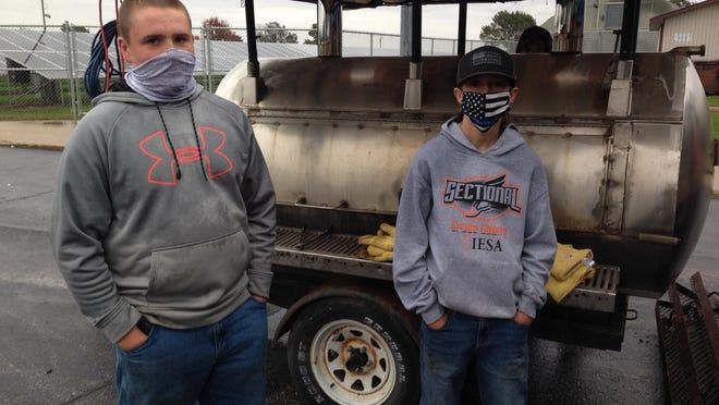 Freshmen FFA members Reid Glaser and Brantson Komnick work the FFA pork chop grill.