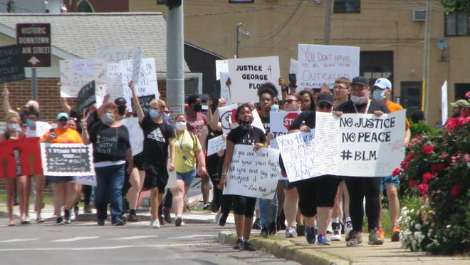 Protesters carry their signs along Mineral Street Tuesday morning.
